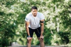 Κουρασμένος αθλητικός τύπος που στέκεται και που στηρίζεται μετά από στο πάρκο Στοκ Εικόνες