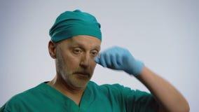 Κουρασμένος αρσενικός γιατρός που αναστενάζει βαθειά, βγάζοντας την ιατρική μάσκα προσώπου, που το brow του απόθεμα βίντεο