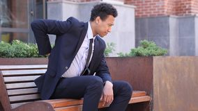 Κουρασμένος αφρικανικός επιχειρηματίας που χαλαρώνει τον πόνο στην πλάτη, έξω από το γραφείο στοκ εικόνες