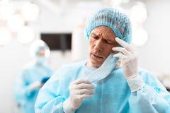 Κουρασμένος γιατρός σχετικά με το κεφάλι του στεμένος με τις προσοχές του ιδιαίτερες στοκ εικόνα