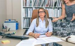 Κουρασμένος γραμματέας με το μέρος της εργασίας στο γραφείο Στοκ Εικόνες
