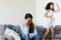 Κουρασμένος εξαντλημένος mom αισθαμένος τον πονοκέφαλο που ενοχλείται από θορυβώδες ενεργό chi στοκ φωτογραφίες