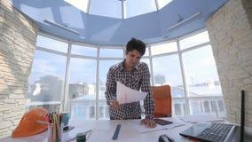 Κουρασμένος, εξαντλημένος, επιχειρηματίας που ρίχνει έναν σωρό των εγγράφων σε ένα καθαρό φωτεινό γραφείο απόθεμα βίντεο