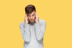 Κουρασμένος επιχειρηματίας ή ο σοβαρός νεαρός άνδρας πέρα από το κίτρινο υπόβαθρο στούντιο με τις συγκινήσεις πονοκέφαλου Στοκ Εικόνα