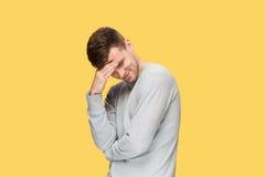 Κουρασμένος επιχειρηματίας ή ο σοβαρός νεαρός άνδρας πέρα από το κίτρινο υπόβαθρο στούντιο με τις συγκινήσεις πονοκέφαλου Στοκ Εικόνες