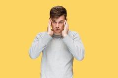 Κουρασμένος επιχειρηματίας ή ο σοβαρός νεαρός άνδρας πέρα από το κίτρινο υπόβαθρο στούντιο με τις συγκινήσεις πονοκέφαλου Στοκ φωτογραφία με δικαίωμα ελεύθερης χρήσης
