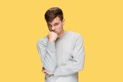 Κουρασμένος επιχειρηματίας ή ο σοβαρός νεαρός άνδρας πέρα από το κίτρινο υπόβαθρο στούντιο με τις συγκινήσεις πονοκέφαλου Στοκ εικόνες με δικαίωμα ελεύθερης χρήσης