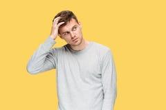 Κουρασμένος επιχειρηματίας ή ο σοβαρός νεαρός άνδρας πέρα από το κίτρινο υπόβαθρο στούντιο με τις συγκινήσεις πονοκέφαλου Στοκ Φωτογραφίες