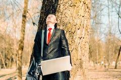 Κουρασμένος επιχειρηματίας κοντά στο δέντρο freelancer στηρίζεται και χαίρεται στον ήλιο στοκ εικόνες με δικαίωμα ελεύθερης χρήσης
