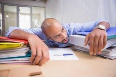Κουρασμένος επιχειρηματίας με το σωρό των αρχείων στο γραφείο Στοκ φωτογραφία με δικαίωμα ελεύθερης χρήσης