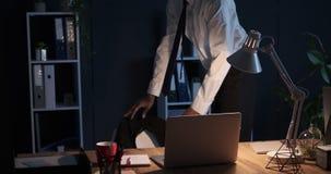 Κουρασμένος επιχειρηματίας που αφαιρεί το παλτό και που κάθεται πίσω στη δουλειά αργά στη νύχτα απόθεμα βίντεο
