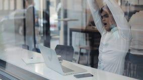 Κουρασμένος επιχειρηματίας που εργάζεται στο lap-top στον άνετο καφέ και που χασμουριέται κατά τη διάρκεια του χρόνου ημέρας απόθεμα βίντεο