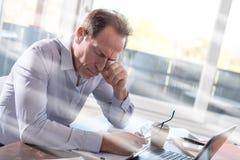 Κουρασμένος επιχειρηματίας που κάθεται την επίδραση στην αρχή, ελαφριών ακτίνων Στοκ Φωτογραφία