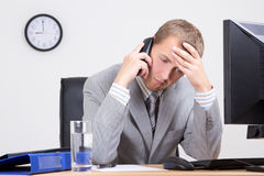 Κουρασμένος επιχειρηματίας που μιλά στο τηλέφωνο στην αρχή Στοκ φωτογραφία με δικαίωμα ελεύθερης χρήσης