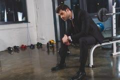 κουρασμένος επιχειρηματίας στο κοστούμι με τη συνεδρίαση ιχνηλατών ικανότητας στη γυμναστική Στοκ Φωτογραφία