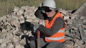 Κουρασμένος εργάτης οικοδομών κοντά σε έναν σωρό των τούβλων φιλμ μικρού μήκους