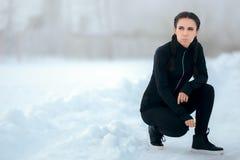 Κουρασμένος θηλυκός δρομέας που στηρίζεται και που δένει τα παπούτσια της το χειμώνα που εκπαιδεύει υπαίθρια Στοκ φωτογραφία με δικαίωμα ελεύθερης χρήσης