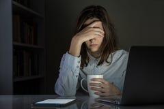 Κουρασμένος και απογοητευμένος θηλυκός εργασιακός χώρος γραφείων προσώπων στο σπίτι αργά τη νύχτα Στοκ Εικόνες