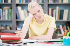 Κουρασμένος και ματαιωμένος σπουδαστής στη βιβλιοθήκη Στοκ εικόνα με δικαίωμα ελεύθερης χρήσης