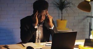Κουρασμένος και τονισμένος επιχειρηματίας με τον πονοκέφαλο που εργάζεται αργά στο γραφείο του Αυτός που εργάζεται σκληρά στο lap απόθεμα βίντεο