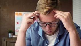 Κουρασμένος κινητός app υπεύθυνος για την ανάπτυξη που κουράζεται στην εργασία που έχει έναν πονοκέφαλο φιλμ μικρού μήκους