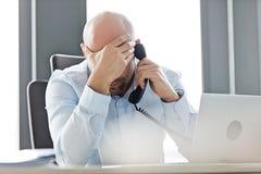 Κουρασμένος μέσος ενήλικος επιχειρηματίας που χρησιμοποιεί το τηλέφωνο γραμμών εδάφους στο γραφείο στην αρχή Στοκ εικόνα με δικαίωμα ελεύθερης χρήσης