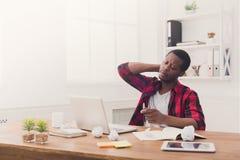 Κουρασμένος μαύρος επιχειρηματίας στο περιστασιακό γραφείο, εργασία με το lap-top Στοκ Εικόνες