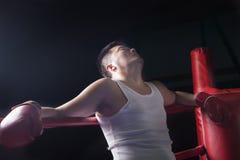 Κουρασμένος μπόξερ που στηρίζεται στα σχοινιά στο εγκιβωτίζοντας δαχτυλίδι, που ανατρέχει στοκ φωτογραφία
