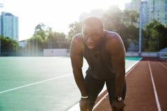Κουρασμένος νέος αφρικανικός αθλητικός τύπος που στηρίζεται μετά από να τρέξει Στοκ Φωτογραφία