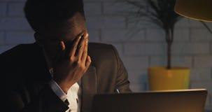 Κουρασμένος νέος επιχειρηματίας που εργάζεται σκληρά στο lap-top του αργά τη νύχτα Νυσταλέα συνεδρίαση ατόμων στο γραφείο στο σκο απόθεμα βίντεο