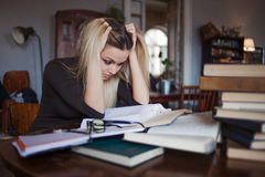 Κουρασμένος νέος σπουδαστής γυναικών του πανεπιστημίου Προετοιμάζοντας το διαγωνισμό και μαθαίνοντας τη βιβλιοθήκη μαθημάτων δημό Στοκ Φωτογραφία