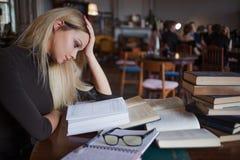 Κουρασμένος νέος σπουδαστής γυναικών του πανεπιστημίου Προετοιμάζοντας το διαγωνισμό και μαθαίνοντας τη βιβλιοθήκη μαθημάτων δημό Στοκ Φωτογραφίες