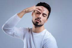 Κουρασμένος νεαρός άνδρας που αισθάνεται κακός στεμένος και σχετικά με το κεφάλι του Στοκ φωτογραφία με δικαίωμα ελεύθερης χρήσης
