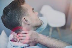 Κουρασμένος νεαρός άνδρας που έχει έναν πόνο στο λαιμό Στοκ Εικόνα
