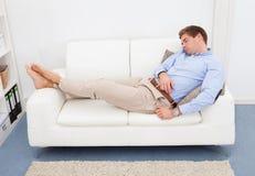 Κουρασμένος νεαρός άνδρας στον καναπέ Στοκ Εικόνες