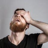 Κουρασμένος νυσταλέος νεαρός άνδρας που απομονώνεται στο γκρίζο υπόβαθρο Στοκ Φωτογραφία