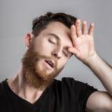 Κουρασμένος νυσταλέος νεαρός άνδρας που απομονώνεται στο γκρίζο υπόβαθρο Στοκ φωτογραφίες με δικαίωμα ελεύθερης χρήσης
