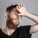 Κουρασμένος νυσταλέος νεαρός άνδρας που απομονώνεται στο γκρίζο υπόβαθρο Στοκ Εικόνες