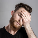 Κουρασμένος νυσταλέος νεαρός άνδρας που απομονώνεται στο γκρίζο υπόβαθρο Στοκ Φωτογραφίες