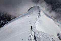 Κουρασμένος ορειβάτης που πηγαίνει πίσω στο καταφύγιο στο ίχνος που τρέχει κατά μήκος της κορυφογραμμής του βουνού  Στοκ Φωτογραφίες