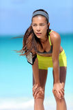 Κουρασμένος δρομέας γυναικών μετά από το workout που αναπνέει παίρνοντας ένα σπάσιμο από το τρέξιμο στην παραλία Στοκ φωτογραφία με δικαίωμα ελεύθερης χρήσης