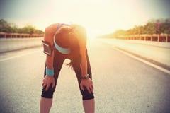 Κουρασμένος δρομέας γυναικών που παίρνει ένα υπόλοιπο μετά από να τρέξει σκληρά