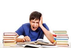 Κουρασμένος σπουδαστής με βιβλία στοκ εικόνες