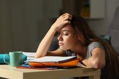 Κουρασμένος σπουδαστής που προσπαθεί να μελετήσει στη νύχτα στοκ εικόνες