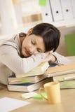 Κουρασμένος σπουδαστής που στηρίζεται στο σωρό των βιβλίων στοκ φωτογραφίες