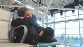 Κουρασμένος ταξιδιωτικός ύπνος εφήβων κοριτσιών στον αερολιμένα που περιμένει τον πάγκο πυλών αναχώρησης αεροπλάνων με όλο τον τρ απόθεμα βίντεο