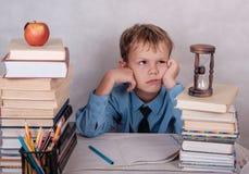 Κουρασμένος των μαθημάτων του ευρωπαϊκού αγοριού στον πίνακα με τα βιβλία Στοκ Φωτογραφίες