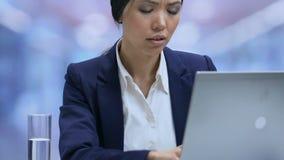 Κουρασμένος υπάλληλος γυναικείων γραφείων που υφίσταται τον ισχυρό πονοκέφαλο και που κλείνει το lap-top, πίεση απόθεμα βίντεο