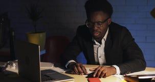 Κουρασμένος ύπνος εργαζομένων γραφείων αφροαμερικάνων αρσενικός στο γραφείο στον υπολογιστή του στο γραφείο που ξυπνά αργά τη νύχ φιλμ μικρού μήκους
