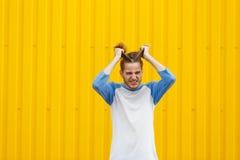 , Κουρασμένο άτομο που τραβά την τρίχα του σε ένα κίτρινο υπόβαθρο Έννοια πίεσης διάστημα αντιγράφων στοκ φωτογραφία